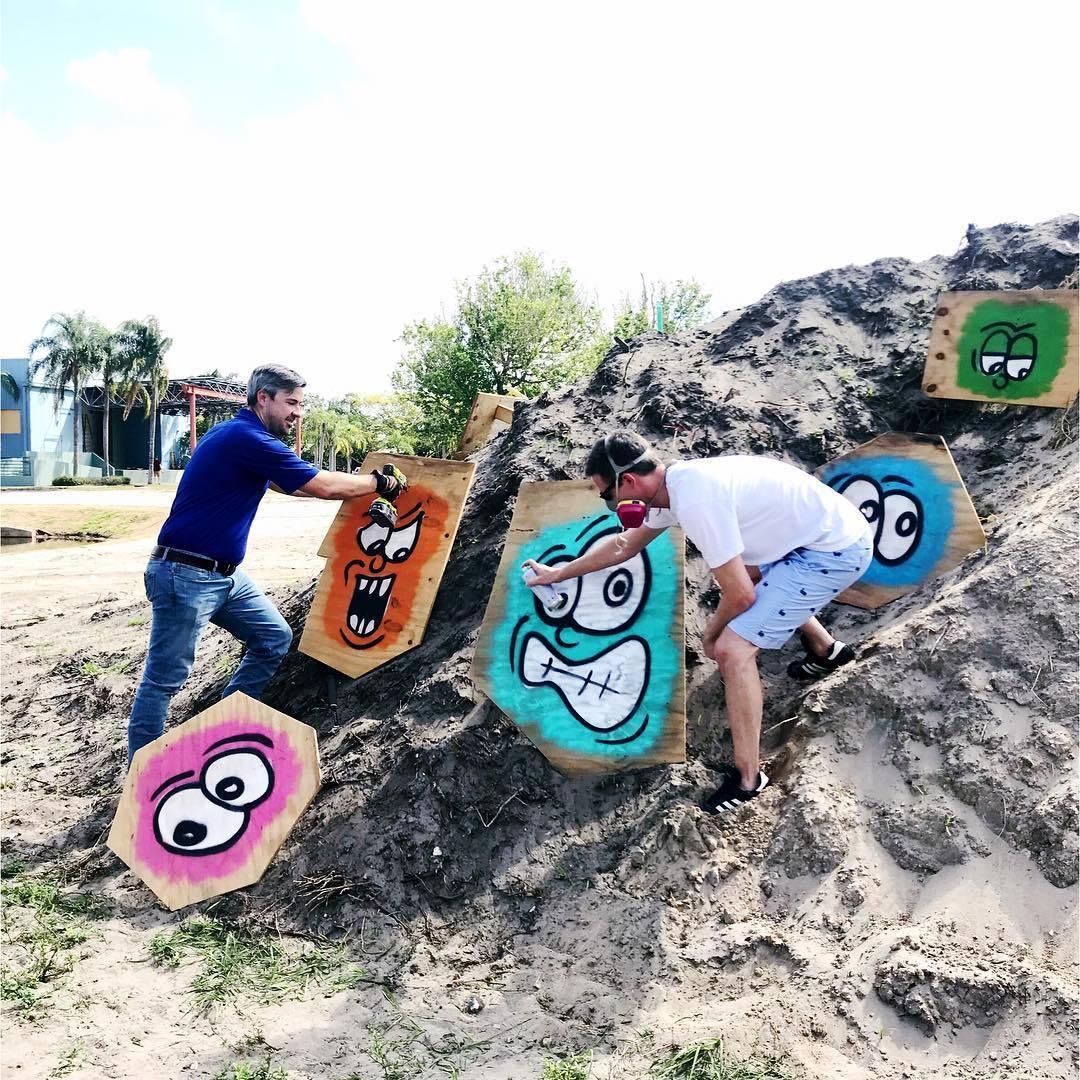"""The Alliance for the Arts is excited to announce David Seitz and Steven Fetterhoff as mystery """"dirt pile"""" artists who draped the eyesore with googly-eyes spray painted on plywood."""